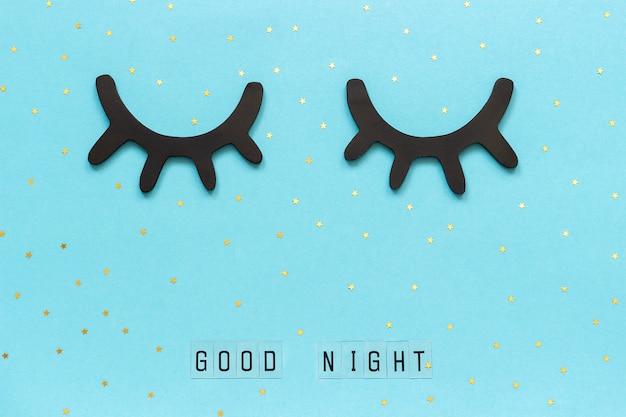 Texto boa noite, cílios pretos de madeira, olhos fechados, estrela dourada. conceito, sonhos doces, saudação