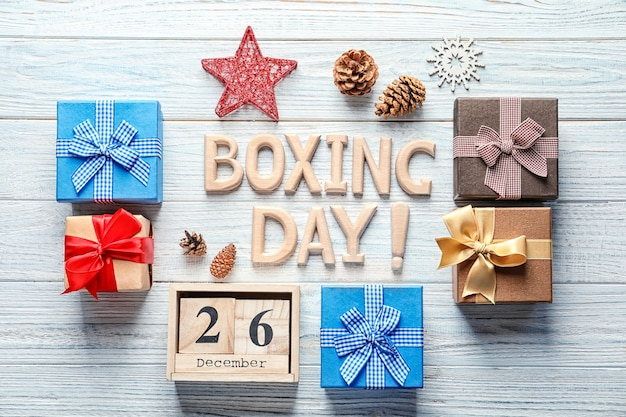 Texto boxing day e caixas de presente em fundo de madeira