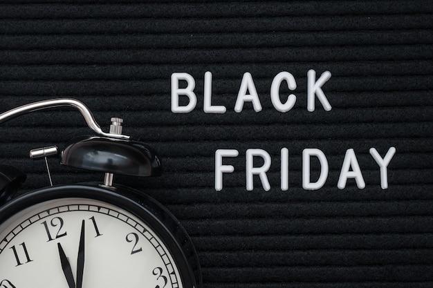 Texto branco sexta-feira preta na placa de letra e no despertador pretos, close up. sexta-feira negra, tempo de vendas da temporada.