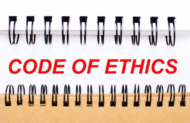 Texto código de ética em papel branco entre blocos de notas espirais brancos e marrons.