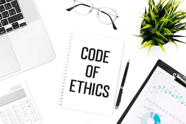 Texto código de ética no caderno. laptop, calculadora, prancheta para gráfico, óculos, caneta e planta na mesa do escritório. camada plana, vista superior. conceito de negócios.