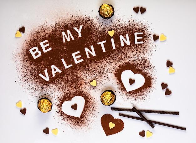 Texto com o conceito de dia dos namorados e três formas de coração de cacau em pó e bombons de chocolate