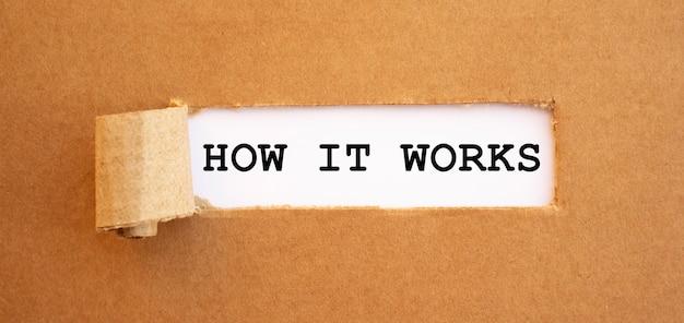 Texto como funciona aparecendo atrás de papel pardo rasgado.