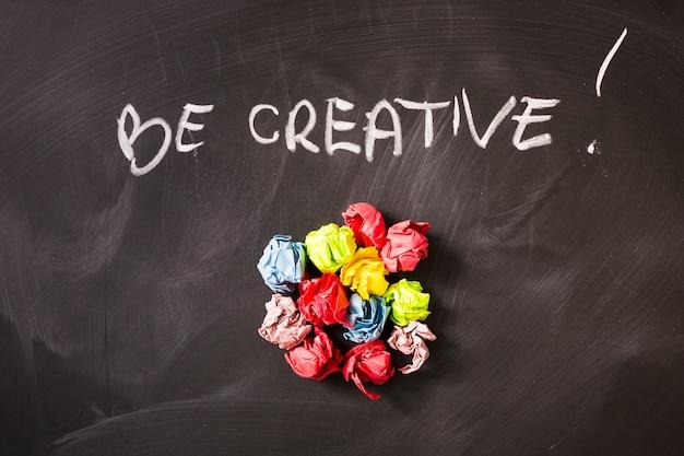 Texto criativo escrito sobre as bolas de papel amassado colorido na lousa