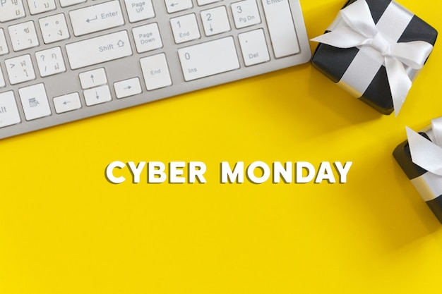 Texto da cyber monday com teclado branco e caixa de presente preta em fundo amarelo