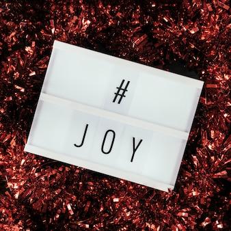 Texto da hashtag joy com enfeites vermelhos