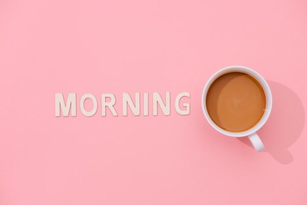 Texto da manhã com uma xícara de café com sombra no fundo rosa.