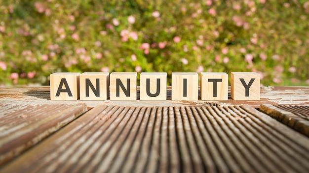 Texto da palavra anuidade em cubos de madeira. flores no fundo