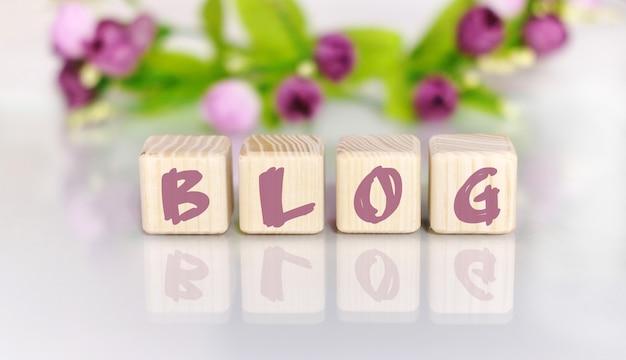 Texto da palavra blog em cubos de madeira à mesa de madeira clara