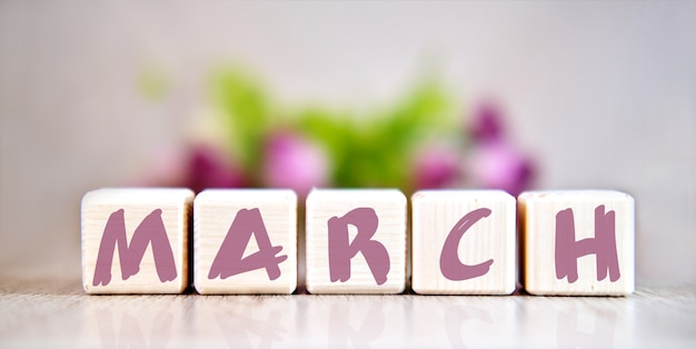Texto da palavra março em cubos de madeira por mesa de madeira clara. flores ao fundo