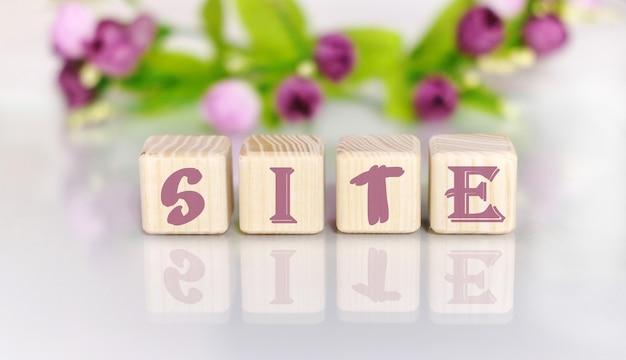Texto da palavra site em cubos de madeira por uma mesa de madeira clara. flores ao fundo