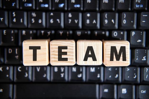 Texto da palavra team em cubos de madeira em um teclado preto