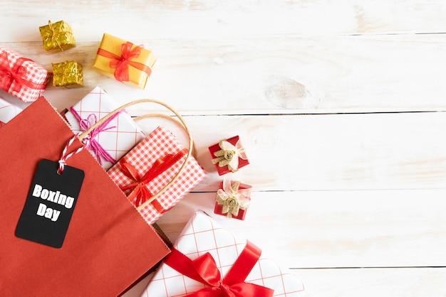 Texto da venda do dia do encaixotamento em uma etiqueta preta com saco de compras e caixa de presente em um fundo de madeira.