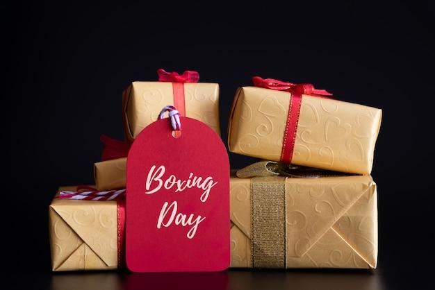 Texto da venda do dia do encaixotamento em uma etiqueta vermelha com a pilha de caixas de presente no fundo preto. sho on-line