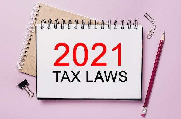 Texto das leis tributárias de 2021 em um bloco de notas branco com espaço para papelaria