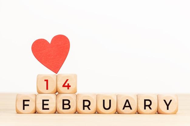 Texto de 14 de fevereiro em blocos de madeira e em forma de coração na mesa. conceito de dia dos namorados.
