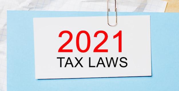 Texto de 2021 leis tributárias em um cartão branco sobre fundo azul. conceito de negócios