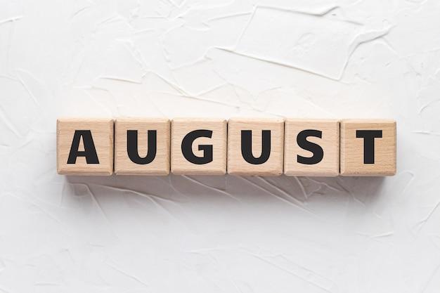 Texto de agosto em cubos de madeira em plano de fundo texturizado branco