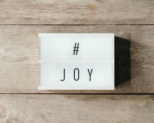 Texto de alegria sobre um painel de led e fundo de madeira