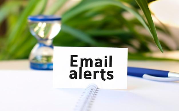 Texto de alertas por e-mail em um caderno branco, ampulheta e caneta azul