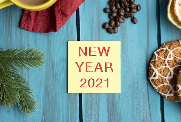 Texto de ano novo de 2021 em papel amarelo em uma mesa de natal decorada