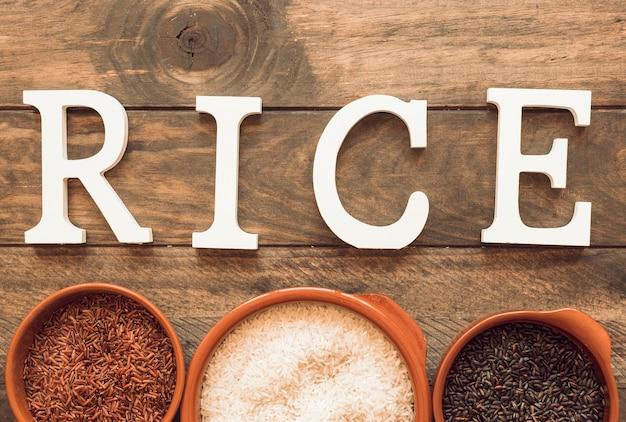 Texto de arroz branco com tigela de arroz na mesa de madeira