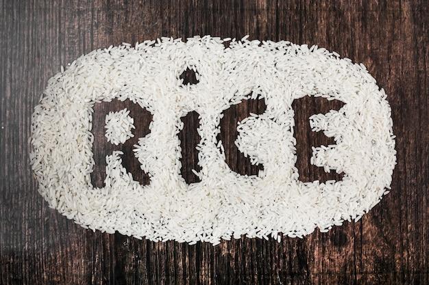 Texto de arroz no plano de fundo texturizado de madeira preto
