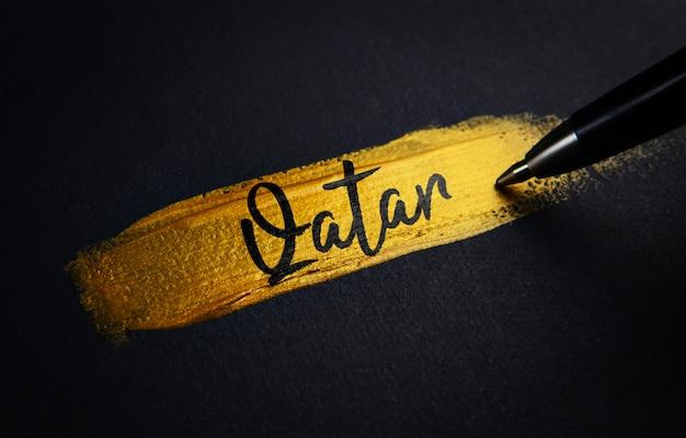 Texto de caligrafia do qatar em pinceladas de tinta dourada