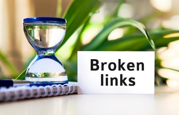 Texto de conceito de negócio de links quebrados em um caderno branco e relógio de ampulheta, folhas verdes de flores
