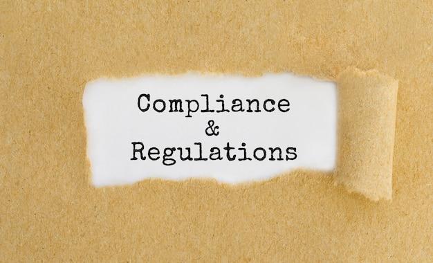 Texto de conformidade e regulamentos aparecendo atrás de papel marrom rasgado