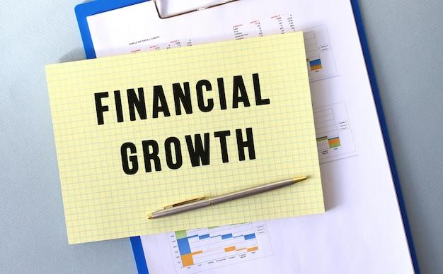 Texto de crescimento financeiro escrito no bloco de notas com lápis. bloco de notas em uma pasta com diagramas. conceito financeiro.