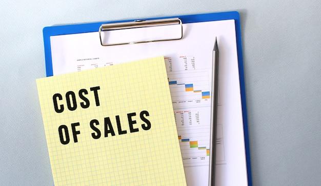 Texto de custo de vendas escrito no bloco de notas com lápis. bloco de notas em uma pasta com diagramas. conceito financeiro.