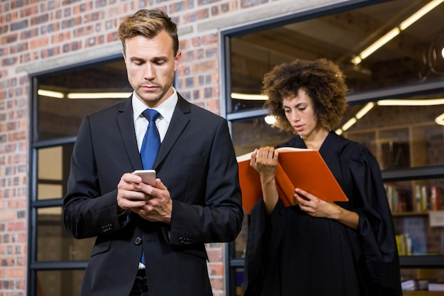 Texto de empresário de mensagens no smartphone e advogado, lendo o livro de lei