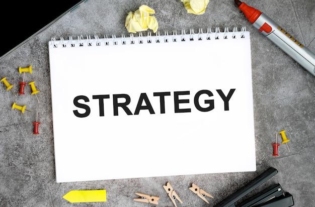 Texto de estratégia em um caderno branco com alfinetes, marcador e grampeador em uma mesa de concreto