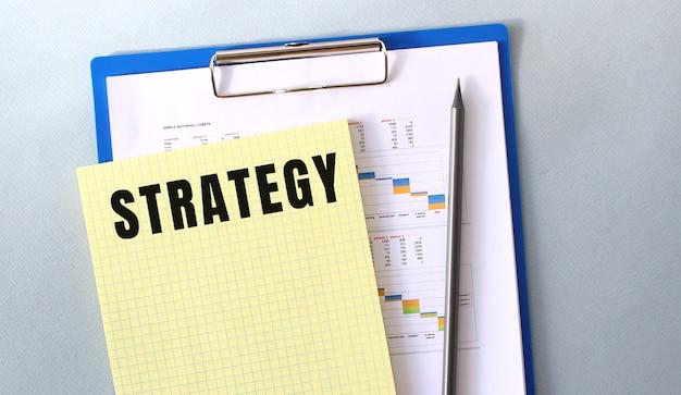 Texto de estratégia escrito no bloco de notas com lápis. bloco de notas em uma pasta com diagramas.