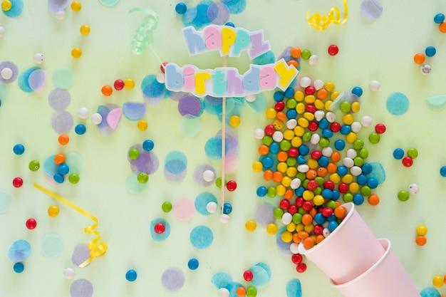 Texto de feliz aniversário, chocolates e itens de festa espalhados sobre a mesa. conceito de celebração de aniversário. vista do topo