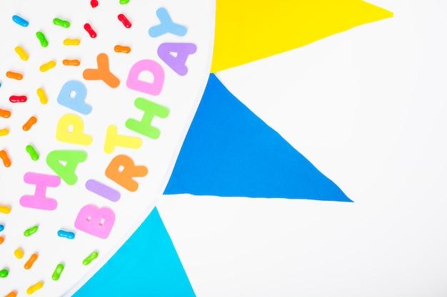 Texto de feliz aniversário com doces e bunting em pano de fundo branco