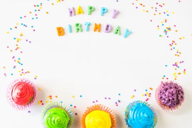 Texto de feliz aniversário com muffins coloridos em pano de fundo branco