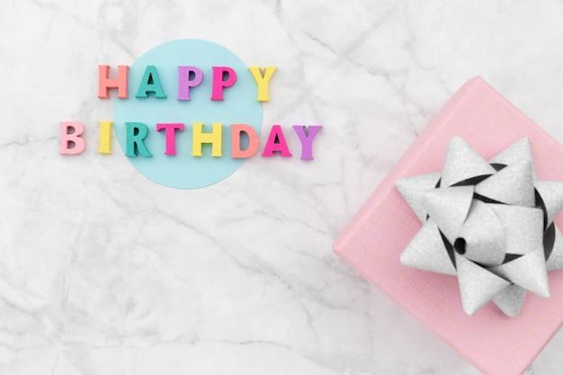 Texto de feliz aniversário de letras coloridas de madeira com caixa de presente.