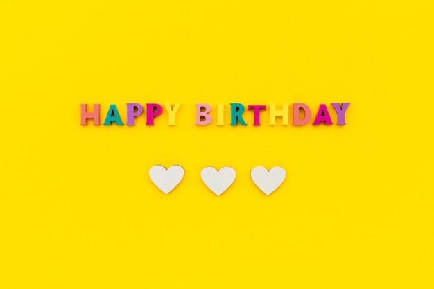Texto de feliz aniversário de letras coloridas de madeira com corações.