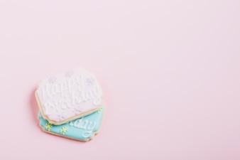 Texto de feliz aniversário em biscoitos frescos sobre fundo rosa