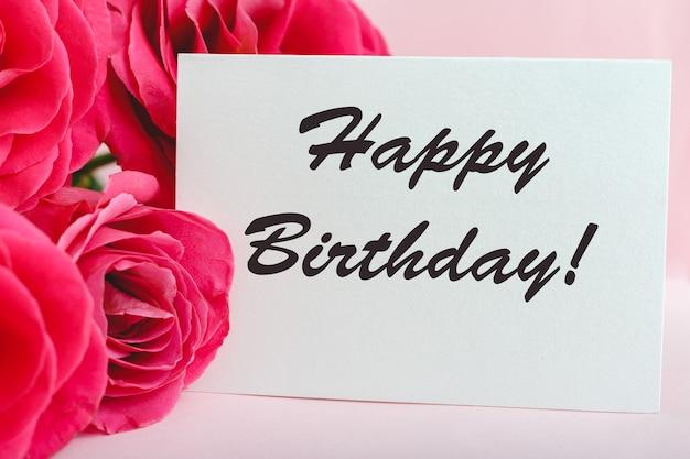 Texto de feliz aniversário no cartão no buquê de flores em fundo rosa. entrega de flores, cartão de felicitações. cartão em rosas vermelhas.