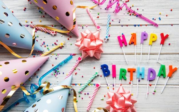 Texto de feliz aniversário por letras de velas com acessórios de aniversário, velas e confetes em madeira branca