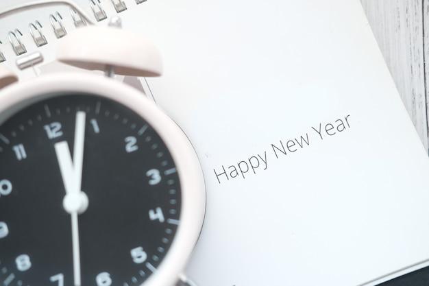 Texto de feliz ano novo no calendário com o relógio na mesa