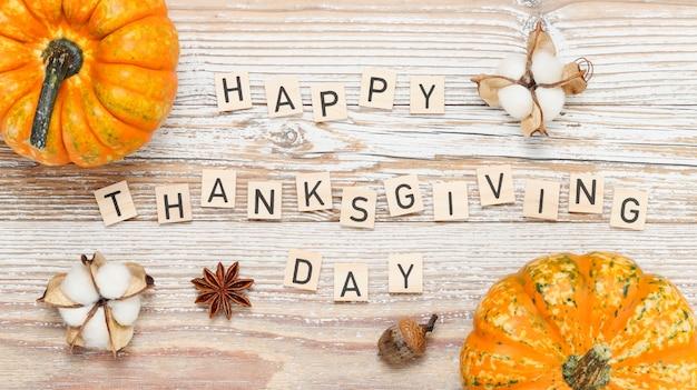 Texto de feliz dia de ação de graças feito de letras de madeira com abóboras e decorações de outono