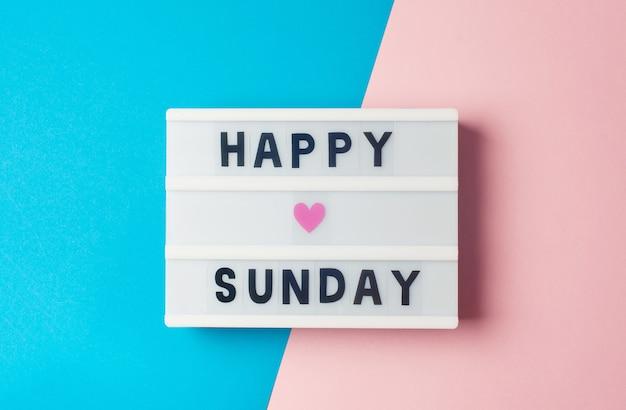 Texto de feliz domingo no display lightbox em fundo azul e rosa