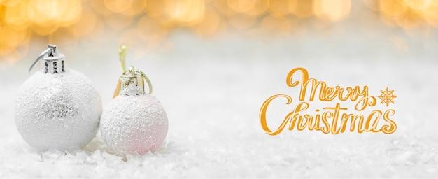 Texto de feliz natal com bolas na neve e luzes desfocadas em estilo laranja