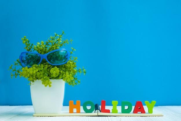 Texto de férias e papel de caderno e pequena árvore