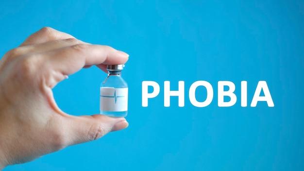 Texto de fobia na mão de um homem segurando um frasco com uma cura para a cura