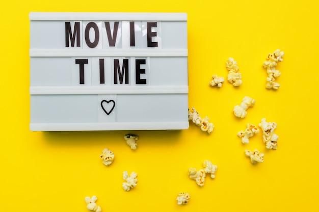 Texto de hora do filme em uma caixa de luz. popconn salgado disperso em fundo amarelo